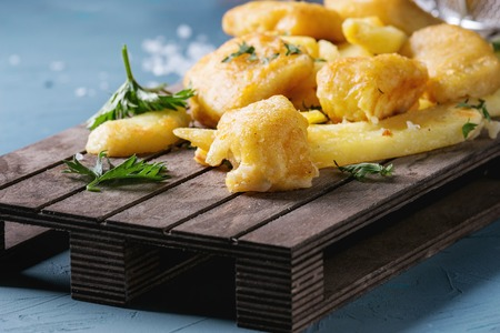 Traditional british fast food fish and chips. Served with lime, parsley, sea salt on wooden serving board over blue concrete background. Close up. Stock Photo