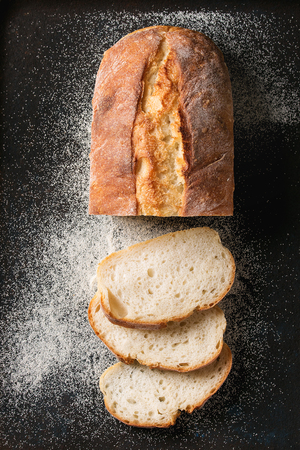 Sliced homemade white wheat bread with wheat flour on old black oven tray as background. Top view