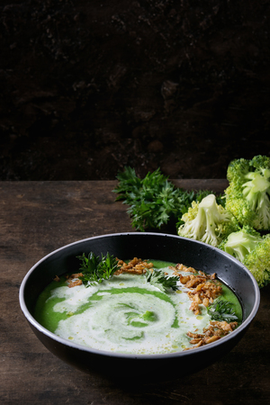 Vegetarian broccoli cream soup served in black bowl with cream, fried onion, fresh parsley and broccoli over old wooden background. Close up. Healthy eating. Stock Photo