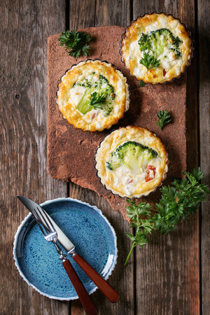 Baked homemade quiche pie in mini metal forms served with fresh greens, plate and cutlery on terracotta board on old plank wooden background. Flat lay with space. Ready to eat