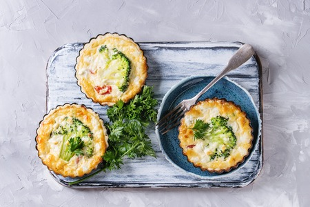 Baked homemade vegetable broccoli quiche pie in mini metal forms served with fresh greens, plate, fork on white serving board on gray concrete background. Flat lay with copy space. Ready for eat