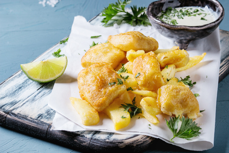 Traditional british fast food fish and chips. Served with white cheese sauce, lime, parsley, on white paper and black serving board over blue concrete background. Close up