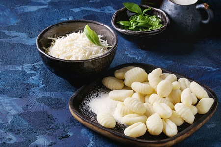 Raw uncooked potato gnocchi in black wooden plates with ingredients. Flour, grated parmesan cheese, pesto sauce, jug of cream, olive oil over dark blue concrete background. Close up. Home cooking.