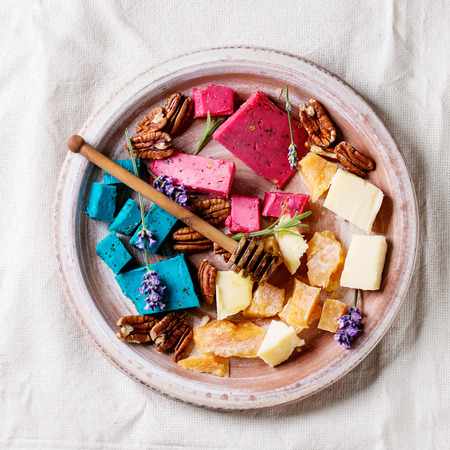 Variety of colorful holland cheese traditional soft, old, pink basil, blue lavender served with pecan nuts, honey, lavender flowers on terracotta plate over white linen background. Flat lay. Square image