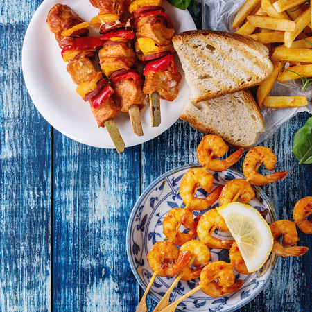 Variety of BBQ snack lunch. Plates grilled spicy prawn kebabs, chicken, pork, vegetables, mushrooms skewers, bread, french fries with sauces and greens over blue wooden background. Flat lay. Square image