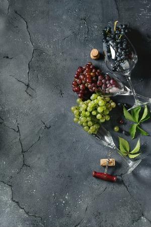 De verscheidenheid van drie type verse rijpe druiven donkerblauw, rood en groen in verschillende het leggen wijnglazen met oude kurketrekker en groene bladeren over zwarte textuurachtergrond. Bovenaanzicht met ruimte. Stockfoto