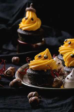 Halloween decorated sweet dessert table black cupcake with orange cream, white meringue ghosts with chocolate eyes on metal tray, leaves and acorn over black tablecloth. Stock Photo