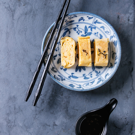 Japanese Rolled Omelette Tamagoyaki sliced with black seasame seeds and soy sauce, served in blue white ornate ceramic plate with chopsticks over blue gray metal background. Top view. Square image