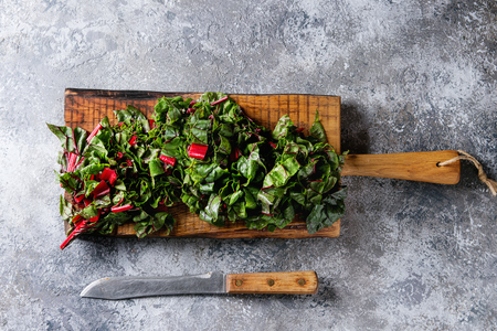 Cutting fresh chard mangold salad on wooden chopping board with knife over gray texture background. Top view with space Stock Photo