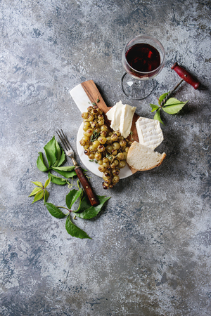 gray texture: Serving board with sliced camembert cheese and baked bunch of green grapes served with bread, glass of red wine, corkscrew, green leaves, fork over gray texture background. Top view with copy space