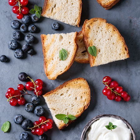 Variety of ingredients for making dessert sandwiches with grilled bread, berries and cream cheese. Red currant, blueberries over gray metal background. Flat lay, summer appetizer concept. Square image