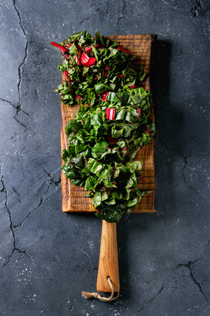 Cutting fresh chard mangold salad on wooden chopping board over black texture background. Top view with space Stock Photo