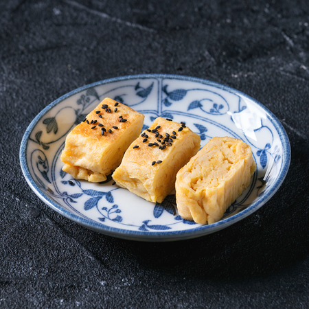 Japanese Rolled Omelet Tamagoyaki sliced with black seasame seeds and soy sauce, served in blue white ornate ceramic plate over black stone texture background. Top view with space. Square image