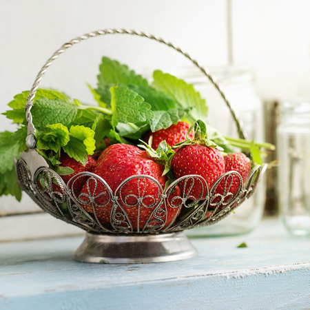 Fresh ripe garden strawberries and melissa herbs in vintage vase standing with empty glass jars for jam on blue white wooden kitchen table. Rustic style, day light, space. Square image Stock Photo