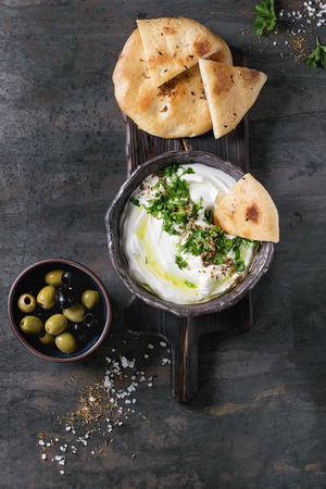 labneh middle eastern lebanese cream cheese dip with olive oil, salt, herbs served with olives, traditional pita bread in terracotta bowl over dark texture metal background. Top view with space Фото со стока