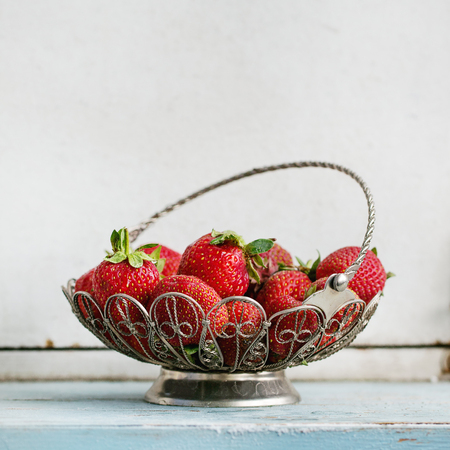 Fresh ripe garden strawberries in vintage vase standing on blue white wooden kitchen table. Rustic style, day light, copy space. Square image