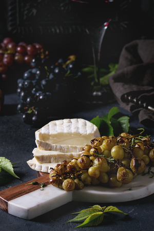 Serving board with sliced camembert cheese and baked bunch of green grapes served with glass of red wine, corkscrew, green leaves over black table. Dark rustic still life Stock fotó