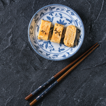 Japanese Rolled Omelette Tamagoyaki sliced with black seasame seeds and soy sauce, served in blue white ornate ceramic plate with chopsticks over black stone background. Top view. Square image