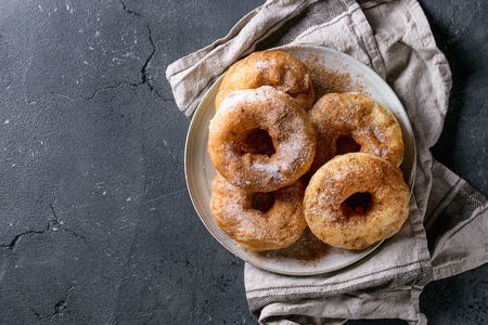 Plate of homemade donuts with sugar and cinnamon powder on gray textile napkin over dark texture background. Top view with copy space