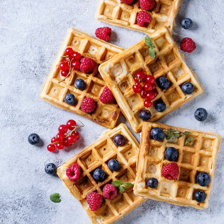 Homemade square belgian waffles with fresh ripe berries blueberry, raspberry, red currant over gray texture background. Top view with space. Square image 免版税图像