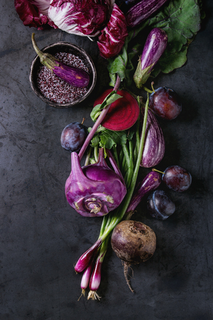 Assortment raw organic of purple vegetables mini eggplants, spring onion, beetroot, radicchio salad, plums, kohlrabi, flower salt over dark metal background. Top view with space Zdjęcie Seryjne