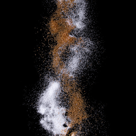 Sifting white and brown cane caster sugar over black background. Isolated. Square image 版權商用圖片