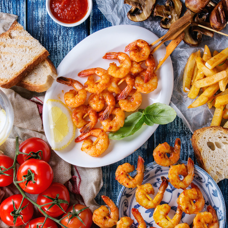 Variety of BBQ snack lunch. Plates grilled spicy king prawn kebabs, mushrooms skewers, bread, french fries potatoes, tomatoes with sauces over blue wooden background. Flat lay. Square image