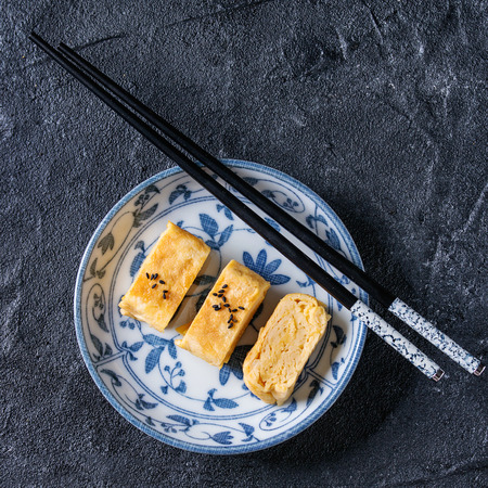 Japanese Rolled Omelet Tamagoyaki sliced with black sesame seeds and soy sauce, served in blue white ornate ceramic plate with chopsticks over black stone texture background. Top view. Square image Stock Photo