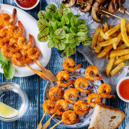 Variety of BBQ snack lunch. Plates grilled spicy king prawn kebabs, mushrooms skewers, bread, french fries potatoes with sauces and greens over blue wooden background. Flat lay. Square image