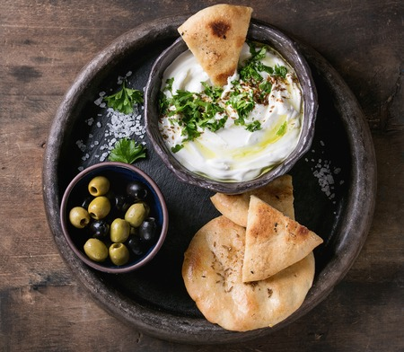 labneh middle eastern lebanese cream cheese dip with olive oil, salt, herbs served with olives, traditional pita bread on terracotta plate over dark texture wooden background. Top view with space