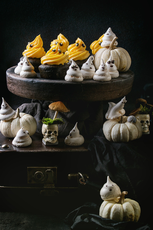 Halloween decorated sweet dessert table black cupcake with orange cream, white meringue ghosts with chocolate eyes, decor skulls and pumpkin over black tablecloth.