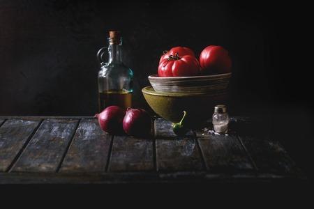 보라색 양파, 고추 및 오래 된 목조 부엌 식탁에 올리브 오일의 병 토마토의 그릇. 어두운 소박한 아직도 인생입니다.