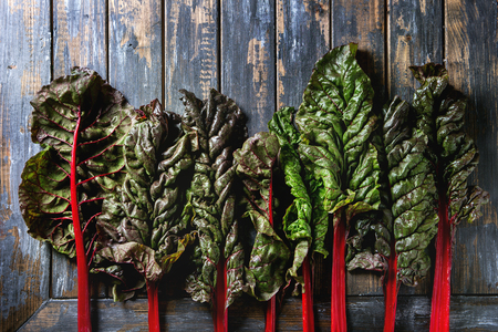 Leaves of fresh organic purple chard mangold over old wooden plank background. Top view with space. Food background.