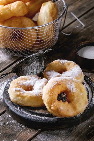 Homemade donuts with sugar powder on black serving board and in frying basket served with vintage sieve on old wooden plank table. Rustic style.