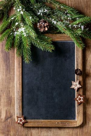 La pizarra vacía de la vendimia con el árbol de navidad del abeto y la decoración moderna de madera protagoniza sobre fondo de madera. Vista superior con espacio para texto