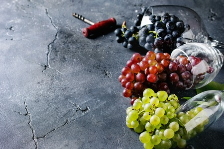 Variety of three type fresh ripe grapes dark blue, red and green in different lying wine glasses with old corkscrew over black texture background with copy space Stock Photo