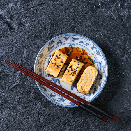 Japanese Rolled Omelette Tamagoyaki sliced with black sesame seeds and soy sauce, served in blue white ornate ceramic plate with chopsticks over black texture background. Top view, space. Square image Stock Photo