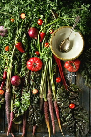 Raw organic purple carrot with variety of vegetables tomatoes, pepper, chard, garlic, onion and empty bowl with spoon on haulm over old wooden plank background. Top view. Food background. Stock Photo