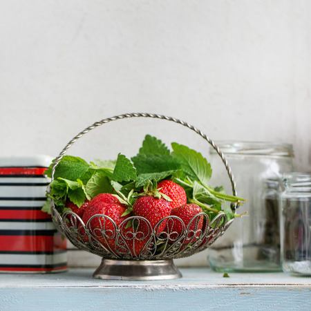 Fresh ripe garden strawberries and melissa herbs in vintage vase standing with empty glass and metal jars for jam on blue white wooden kitchen table. Rustic style, day light, copy space. Square image Stock Photo