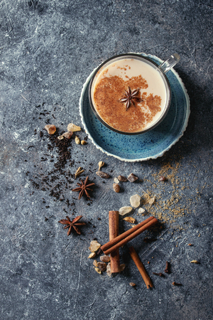 Glass cup of traditional indian masala chai tea on blue saucer with ingredients above. Cinnamon, cardamom, anise, sugar, black tea over dark texture background. Top view with space Stock Photo