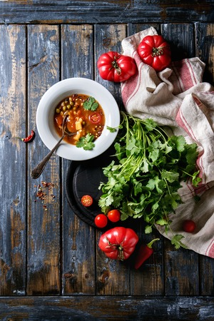 Vegetarian hot carrot tomato pea potato soup, served in white plate with fresh coriander and tomatoes on kitchen towel over old wooden plank table. Top view with space Stock Photo