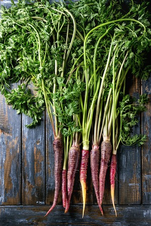 Bundle of raw organic purple carrot with green top haulm over old wooden plank background. Top view with space. Food background. 版權商用圖片