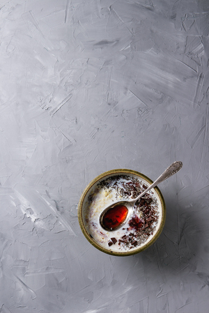 Bowl of milk cereal porridge with additives jam, chocolate, chia seeds and berries, served with spoon over gray texture background. Top view with space Stock Photo