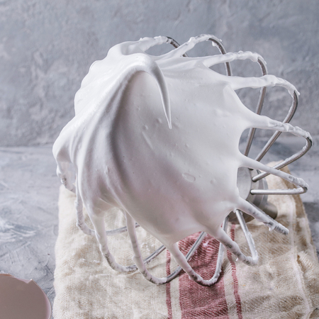 Process of cooking meringue. Whipped egg whites on mixer whisk with broken eggs on linen towel over gray texture background. Baking dessert concept. Close up. Square image