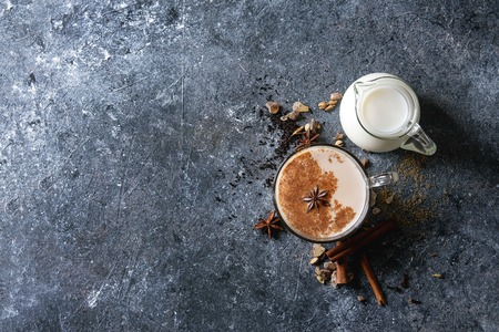 Glass cup of traditional indian masala chai tea with ingredients above. Cinnamon, cardamom, anise, sugar, black tea, jug of milk over dark texture background. Top view with copy space Stock Photo
