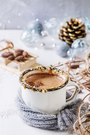 Vintage mug in wool scarf of hot chocolate, decor with nuts, caramel, spices. Ingredients and Christmas toys above over white texture background with space. Stock Photo