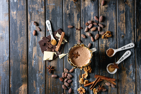 ホットチョコレートのヴィンテージマグ、ナッツ、キャラメル、スパイスで装飾。食材上記.刻んだダークとホワイトのチョコレート、カカオ豆、古 写真素材