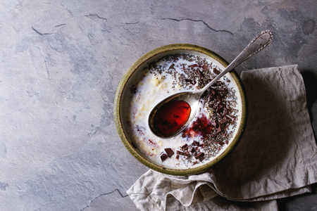 Bowl of milk cereal porridge with additives jam, chocolate, chia seeds and berries, served with spoon over gray kitchen table. Top view with space Stock Photo