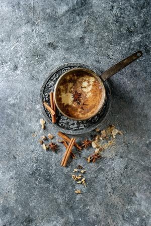上記の食材を使った伝統的なインドのマサラチャイのヴィンテージポット。シナモン、カルダモン、アニス、砂糖暗い質感の背景。コピースペース