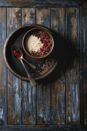 Bowl of milk cereal porridge with additives flax seeds, chocolate and berries over old wooden plank background. Top view with space
